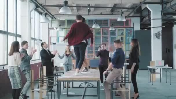 Kollegen feiern das Ende der Arbeitswoche, haben Spaß beim Tanzen auf dem Tisch und werfen Papier hoch. Erfolg. Corporate Party Business Team. moderne trendige Büroeinrichtung. Mitarbeiter unterhalten