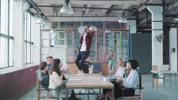 The manager is dancing on the table and singing in a megaphone. His colleague throws money away. Employees celebrate success. Corporate party business team. Modern trendy office interior