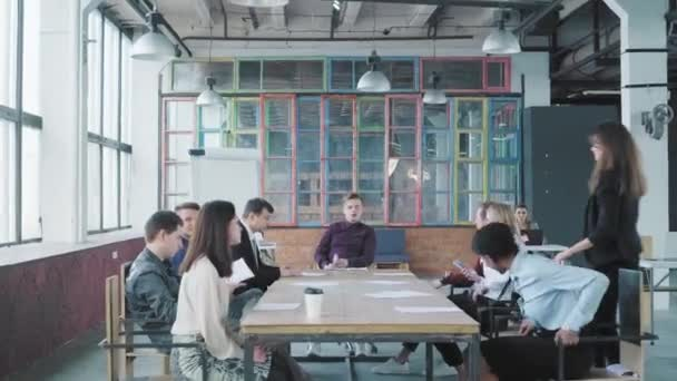 Colleagues sit at a large table and hold a meet up in modern trendy office. Manager swings in an office chair. Start up. Business team. Coworking. Office life