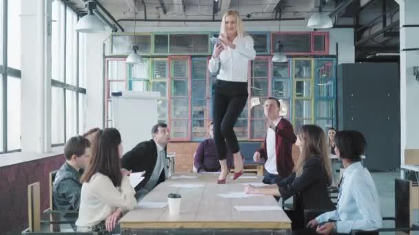 Obchodní žena stojí na stole, začíná tančit a rozsévá peníze a dokumenty. Její kolegové oslavují svůj úspěch. Podnikový obchodní tým. Interiér módní kanceláře. Život v kanceláři