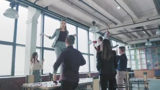 Colleagues celebrate the end of the project, have fun dancing on the table. Managers enjoy success and victory. Corporate party business team. Modern trendy office interior. Coworking. Office life