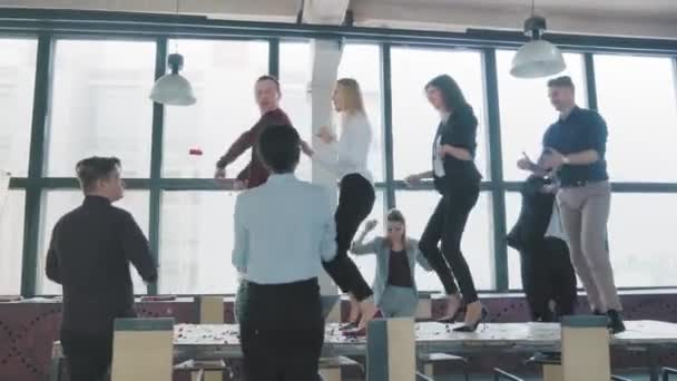 Employees celebrate the end of the project, have fun dancing on the table. Confetti fly around. Managers enjoy success and victory. Corporate party business team. Coworking