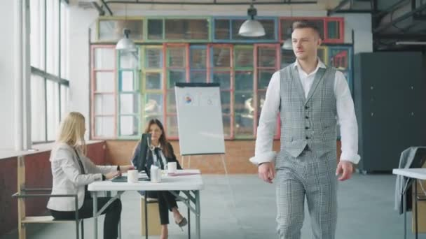 A businessman in the office jokes, walks up to a colleague, sits down at the table, looks at the documents and throws them away. The manager colleague is outraged. Trendy office interior. Coworking