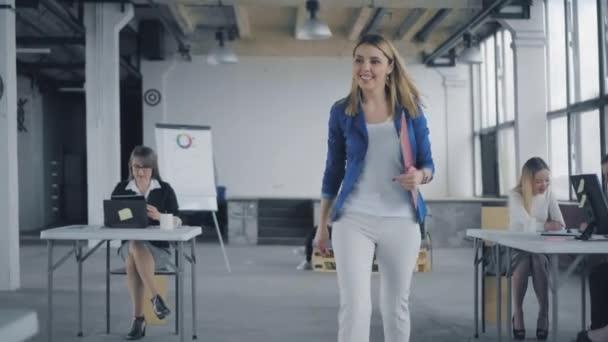 Vedoucí ženy v bundě chodí kolem kanceláře, komunikuje s kolegy a dává jim úkoly. Pracuju na tom. Život v kanceláři. Interiér moderního módní kanceláře ve stylu podkroví