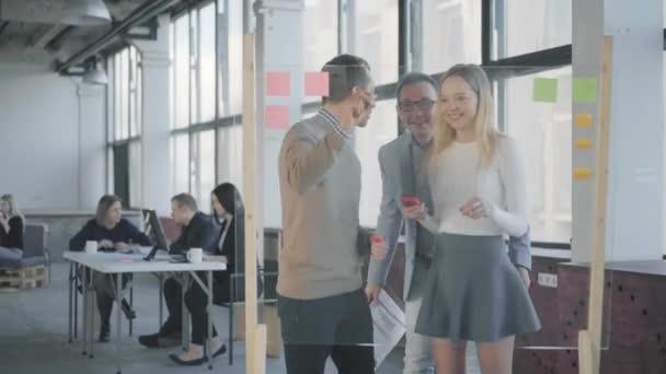 Office munkafolyamatba. Kollégák mosolyognak, és megbeszélése üzleti feladatokat rajz grafikák és beillesztés matricákat egy Glass Board. Coworking. A Hivatal életében. Modern, trendi irodabelső