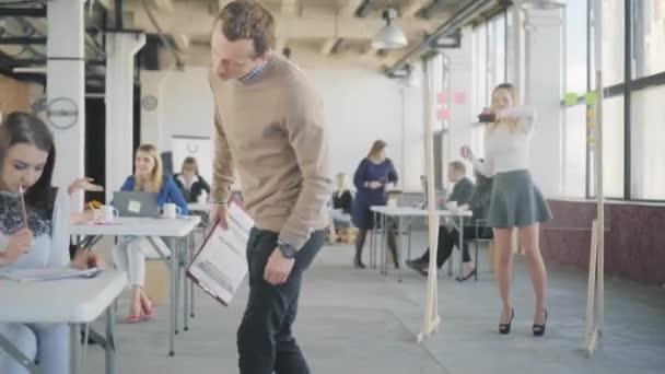 Mladý manažer chodí po kanceláři, komunikuje s kolegy a dává jim úkoly. Pracuju na tom. Pracovní postup sady Office. Interiér moderního kancelářského stylu v podkroví. Pohled zezadu