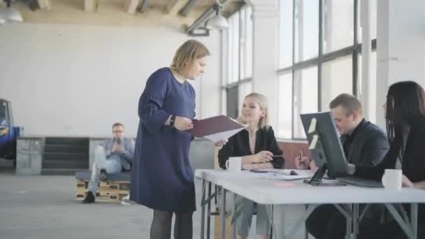 Ženská účetní chodí po kanceláři, komunikuje s kolegy a dává jim dokumenty. Pracuju na tom. Život v kanceláři. Interiér moderního módní kanceláře ve stylu podkroví
