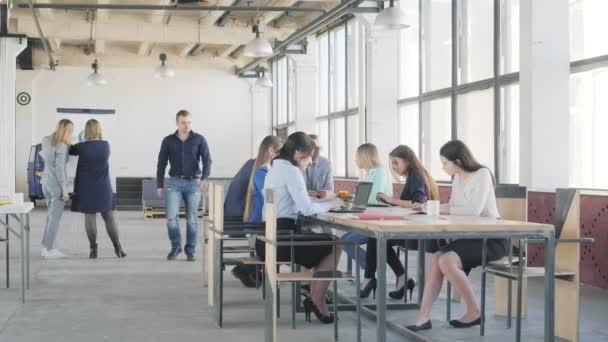 Zaměstnanci sedí a drží schůzku u velkého stolu. Manažer se k nim přiblíží a sedí u stolu. Téměř dva kolegové dělají prezentaci na flipchart. Život v kanceláři. Spolupracujete