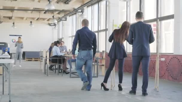 Employees prepare a presentation near the glass board, after which they come up and sit at the table where the business team holds a meeting. Coworking. Loft style office space