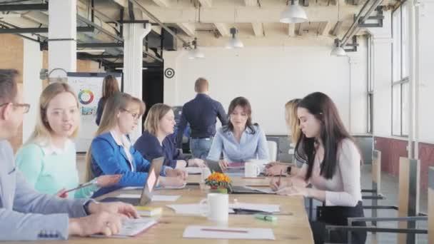 Obchodní tým má schůzku v kanceláři ve stylu podkroví. Dva kolegové dokončí přípravu prezentace na flipchart a pojedou na svá pracoviště. Život v kanceláři. Spolupracujete