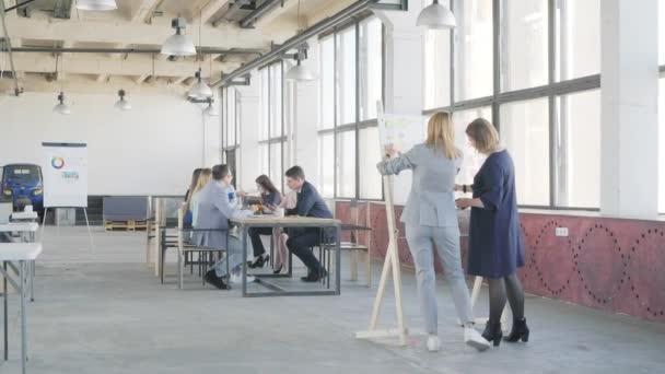 Dva zaměstnanci připravují prezentaci na skleněné desce. Na pozadí je schůzka obchodního týmu. Interiér ve stylu podkroví. Život v kanceláři. Spolupracujete
