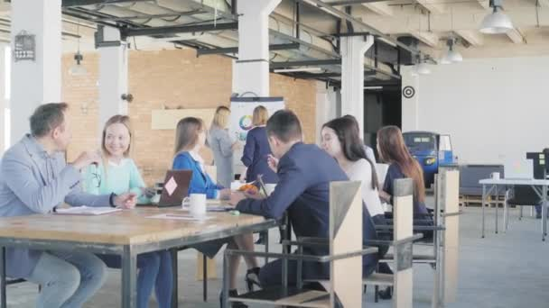 A team of engineers holds a meeting at a large table. In the background, two female employees are preparing a presentation near the flipchart. Interior in loft style. Office life. Coworking