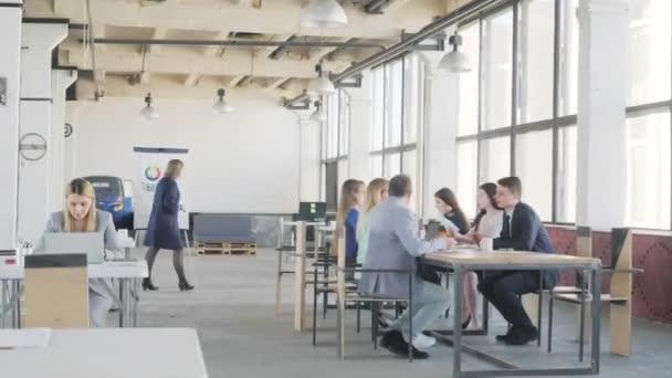 Obchodní tým na velkém stole pořádá schůzku. Nedaleko od něj kolega dokončí přípravu prezentace na flipchart, vejde se na kolegu, vezme si houbičku a odchází. Spolupracujete