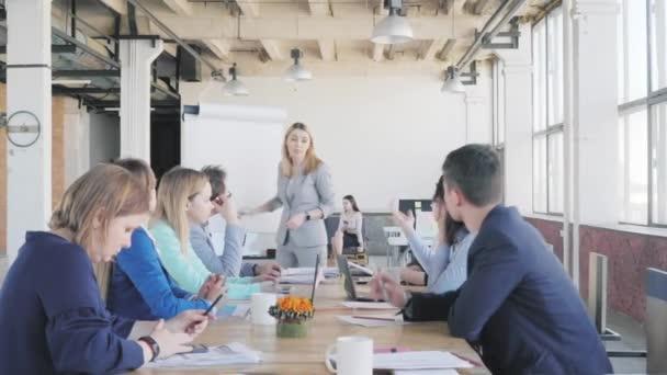 Vedoucí týmu provádí prezentaci pomocí flipchart, popisuje obchodní procesy a zabývá se kolegy. Zaměstnanci sedí u stolu. Život v pozadí. Spolupracujete