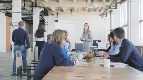Vedoucí oddělení obchodní skupiny v obchodním obleku rozebírá obchodní procesy s kolegy a vytváří prezentaci pomocí flipchart. Zaměstnanci sedí u stolu. Životnost kanceláře na pozadí