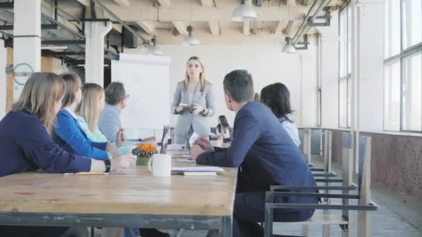 The team leader discusses with colleagues and conducts a presentation using a flipchart, describes business processes. Employees sit at the table. Office life. Coworking. Modern interior in loft style