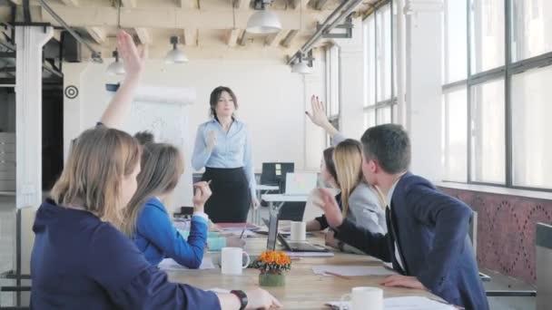 Zaměstnanci důkladně diskutují o prezentaci a sedí u stolu. Vedoucí ženského týmu komunikuje s kolegy, odpovídá na otázky a kreslí na flipchart. Život v kanceláři. Spolupracujete