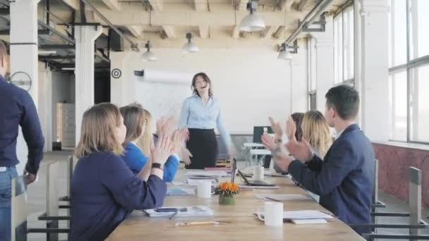 Kolegové poděkují veliteli týmu za úspěšný projekt a tleskají při sezení u stolu. Obchodní žena dokončí prezentaci a sedne se. Život v pozadí. Spolupracujete