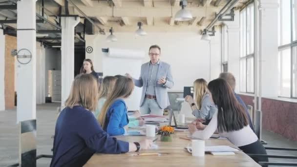 hält ein Geschäftsmann eine Präsentation mittels Flipchart und kommuniziert mit Kollegen. Mitarbeiter sitzen mit am Tisch. Büroleben im Hintergrund. Coworking. Modernes Interieur im Loftstil