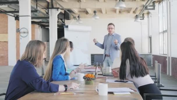 Business Team je zábavný při projednávání prezentace. Mužský manažer odpoví na otázky zaměstnanců, kteří sedí u velkého stolu poblíž flipchart. Život v kanceláři. Spolupracujete