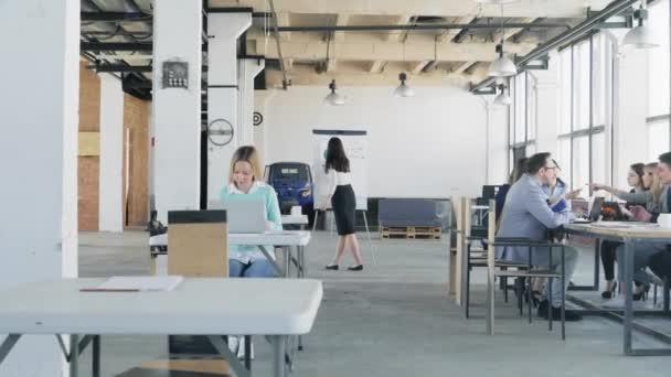 Kamera prochází kanceláří. Obchodní tým na velkém stole pořádá schůzku. Blízká kolegyně kreslí grafiku na skleněné desce. Život v kanceláři. Spolupracujete