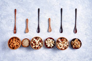 pecans, hazelnuts, almonds, pine nuts, cashews in wooden bowls on blue background, top view, flat lay