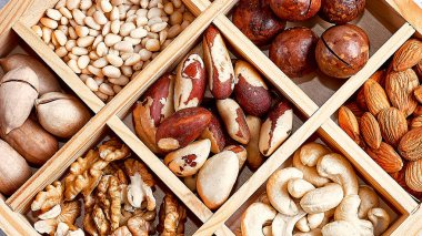 pecans, hazelnuts, almonds, pine nuts, brazil nut, cashews in a wooden box on blue background, top view, flat lay