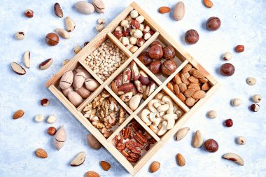 Assortment of nuts in a wooden box, on a blue background. pecans, hazelnuts, almonds, pine nuts, brazil nut, cashews, Top view, flat lay.