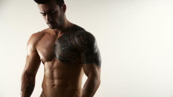 Culturista senza camicia muscolare che flette in studio
