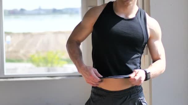 I giovani misura luomo mettere sulla camicia il torso muscoloso nudo
