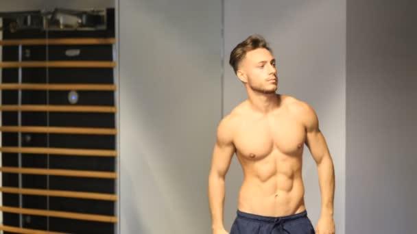 Sportovní mladý muž svlékání v tělocvičně