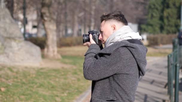 Pohledný mladý muž fotograf pořizování fotografie mimo