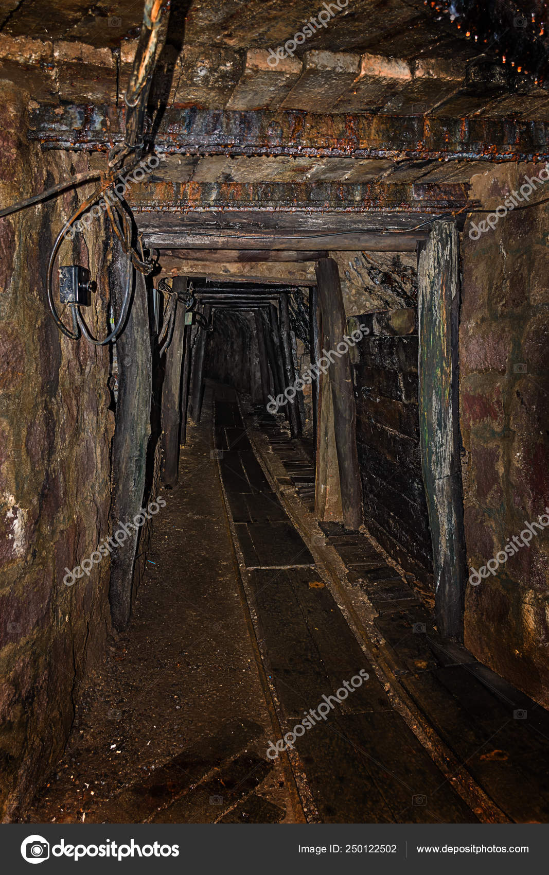 Empty old abandoned mine shaft with wooden timbering and