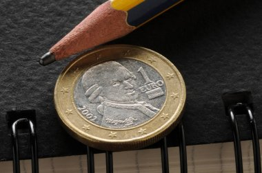 Austrian euro over a notebook with spiral and pencil