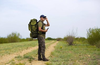 A traveler is walking along the road with a backpack