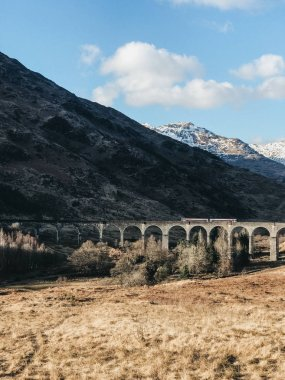 View of a train on Glenfinnan Viaduct, Glenfinnan, Scotland, on a sunny spring day.