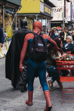 New York, USA - May 28, 2018: People dressed in Batman and Spiderman costumes walk through Times Square, a major commercial and entertainment centre and neighbourhood in Midtown Manhattan, New York.