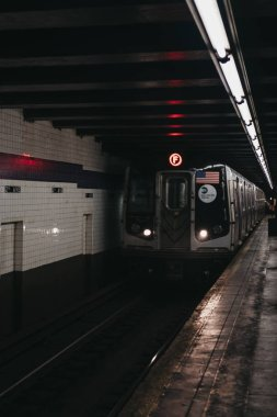 New York, USA - May 29,  2018: F Line Train arriving at a station platform in New York. New York City Subway is one of the world's oldest public transit systems.