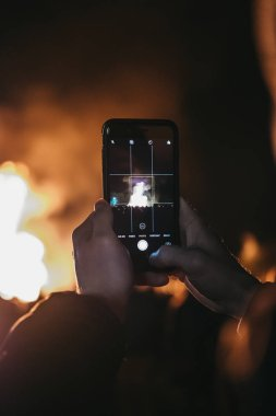 London, UK - November 3, 2018: Man taking photo of bonfire on mobile phone at Guy Fawkes Night yearly celebration in Alexandra Palace, London.