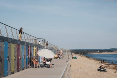 Milford on Sea, UK - July 13, 2019: People relax by new beach huts in Milford on Sea, UK. Opened in May 2017, they replaced 119 concrete huts which were severely damaged in a violent storm in 2014. stock vector