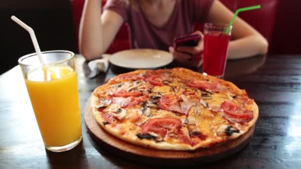 Příležitostná dívka pomocí smartphone v kavárně. Čerstvý džus a pizza v popředí.