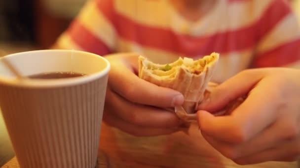 Kavkazské mladík jíst chutné shawarma v pita chlebu s čaj nebo káva, posezení v kavárně. Detailní záběr.