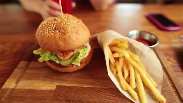 Šťavnatý burger s kuřecím masem, hranolky, omáčka a šťávy. Smowmotion