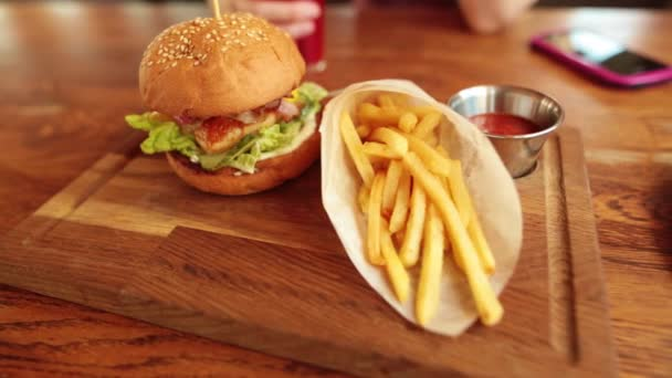 Side view of tasty chicken burger with french fries, sauce and juice. Smowmotion.