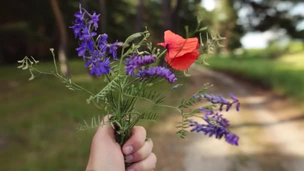 Man holding a bouquet of wildflowers in his hand. Travel concept.