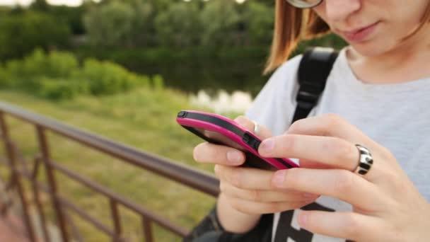 Trendi csípő lány textil és kommunikáció segítségével okostelefon.