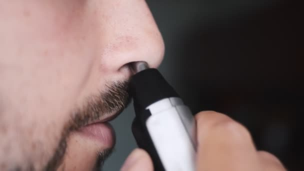 Handsome young man remove hair from his nose with trimmer