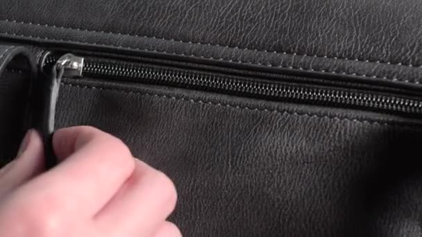Young woman opening the zipper of a ladies handbag. Closeup of female hand.