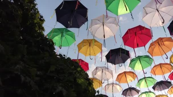 Multicolored umbrellas on the street against the sky swinging in the wind.