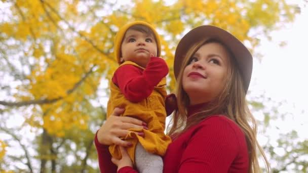 Multietnické rodina. Matka a malá dcera hraje v podzimním parku večer.